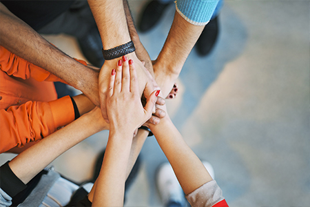 Group of people in circle with hands stacked in the middle