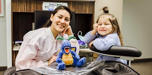 Smiling team member and child in dental exam room