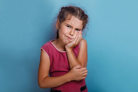 A young girl holding her cheek in pain