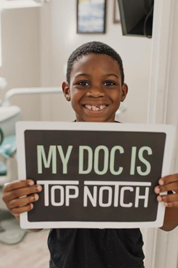 Child holding a sign that says my Doc is top notch