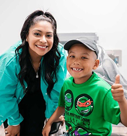 Dental team member and young patient giving thumbs up