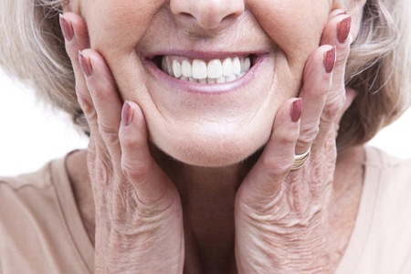 close up older woman holding her face and smiling with dental implants in Mesquite