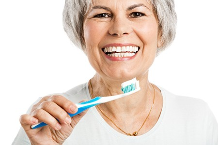 An older woman holding a toothbrush.