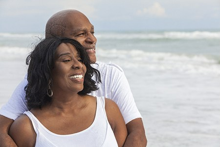 An older couple smiling and hugging at the beach.