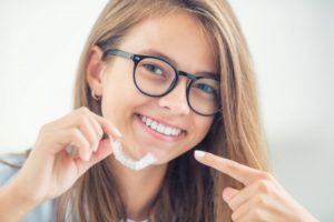 Smiling teen with glasses points to her Invisalign in Mesquite